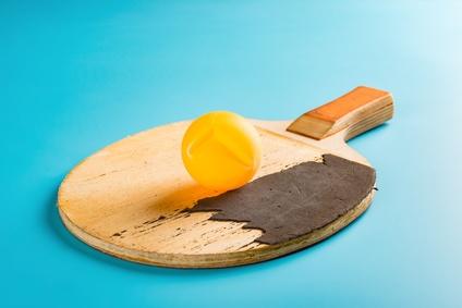 Tischtennisschläger mit einem kaputten Ball und Belag